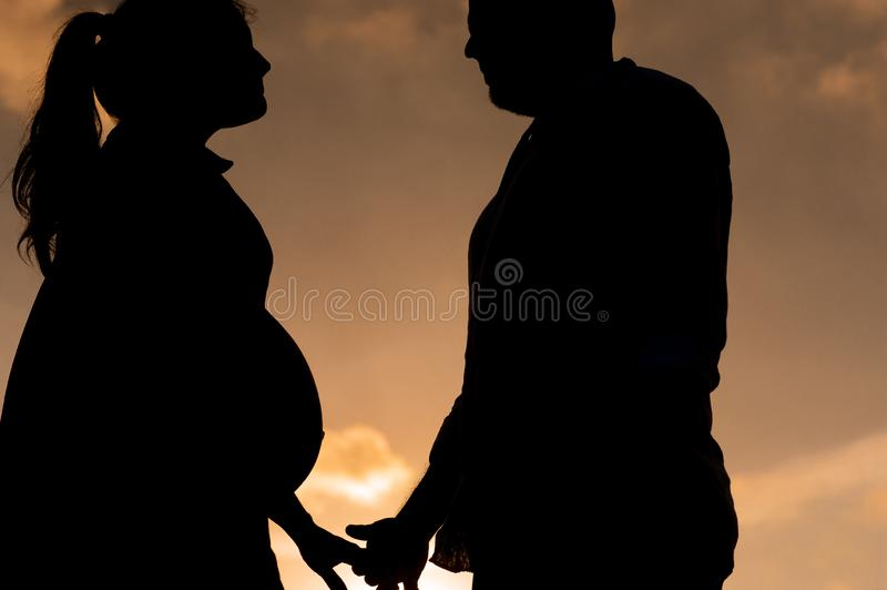 Silhouette of young couple in love looking at each other at sunset with woman pregnant holding hands royalty free stock photo