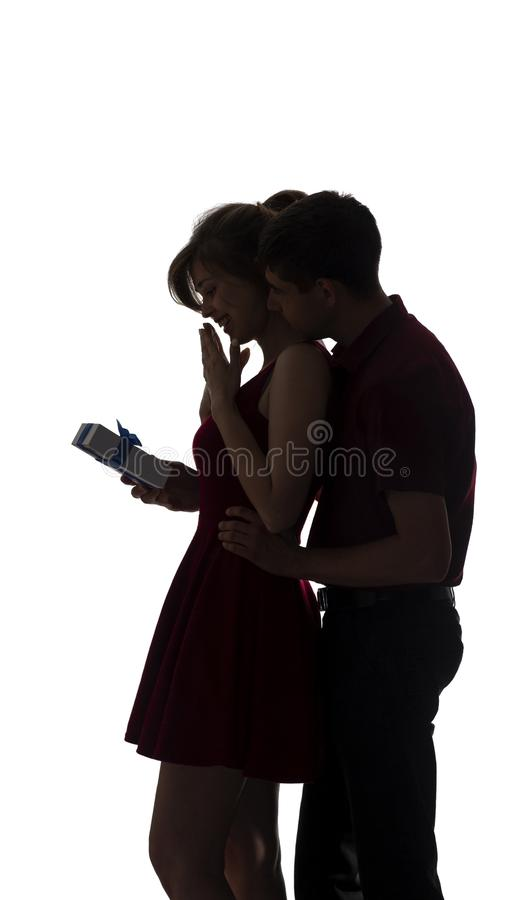 Silhouette of a young couple in love on white isolated background, man came up behind to woman to make a surprise with box present royalty free stock images