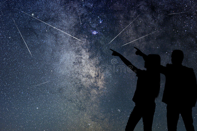 Silhouette of young couple watching Meteor Shower. Nigh Sky. Meteor Shower royalty free stock photo