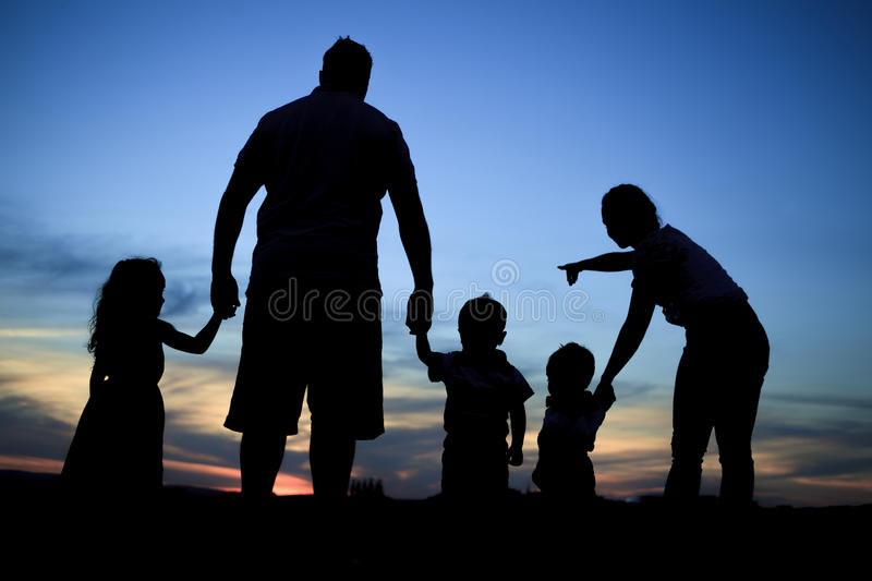 Silhouette of a young family with some childs. A Silhouette of a young family with some childs standing at the sunset. The mother is pointing something royalty free stock photography