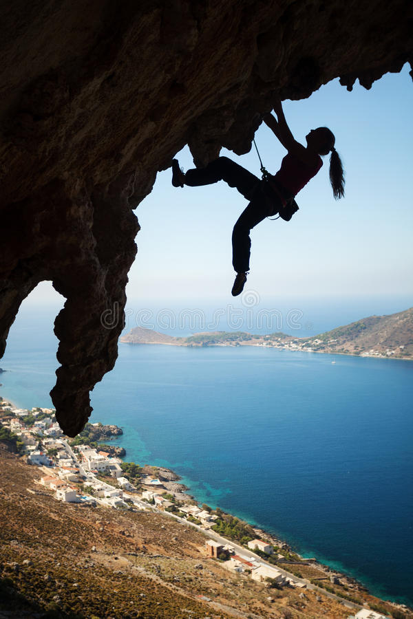 Silhouette of young female rock climber on a cliff royalty free stock images