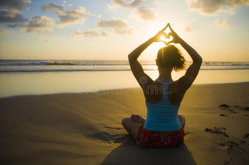Silhouette of young fit sport woman in beach sunset yoga practice in meditation doing heart shape with hands and fingers against t stock images