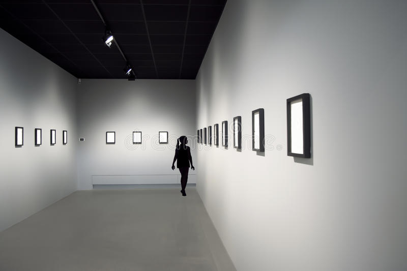 Silhouette of young girl at art exhibition. In a room with straight lines and high contrasts of black and white royalty free stock image