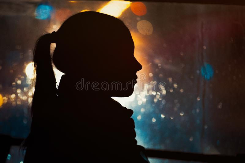 Silhouette of young girl on night city bokeh background. Rain drops running down the window. Autumn season stock photos