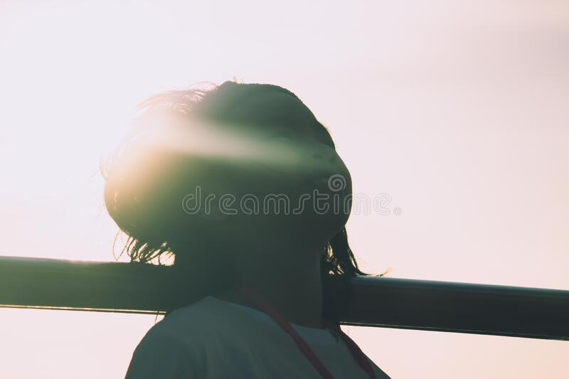 Silhouette Young girl relaxing on a vacation with sunshine behind her back stock image