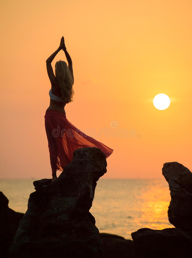 A silhouette of a young girl on rock at sunset 2 stock photos