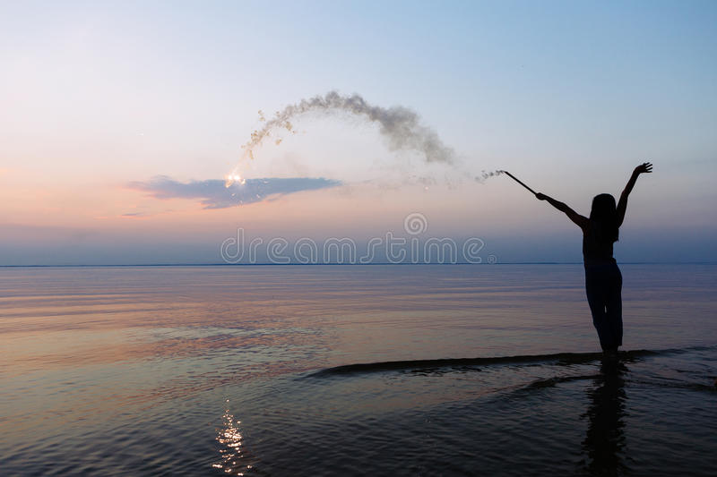 The silhouette of a young girl shooting fireworks during sunset at the ocean beach. stock photography