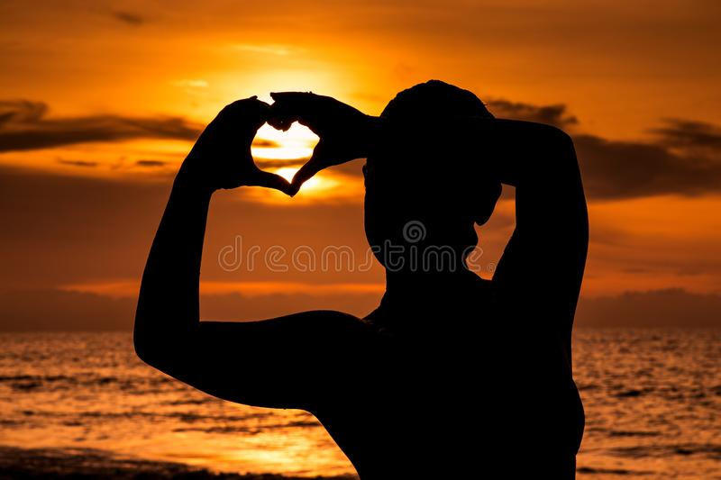 Silhouette of young girl with sunset on the beach, forming the shape of a heart with hands. stock photos