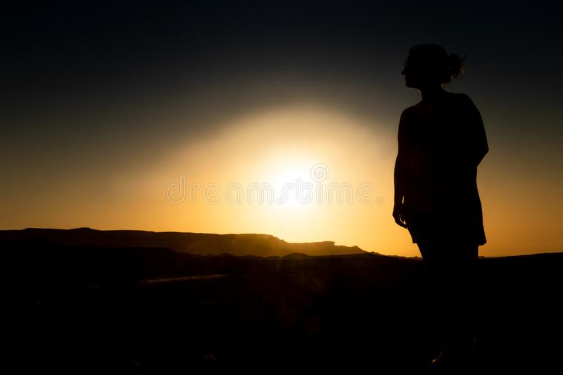 Silhouette of young girl with sunset in Namibe Desert. Africa. Angola royalty free stock images