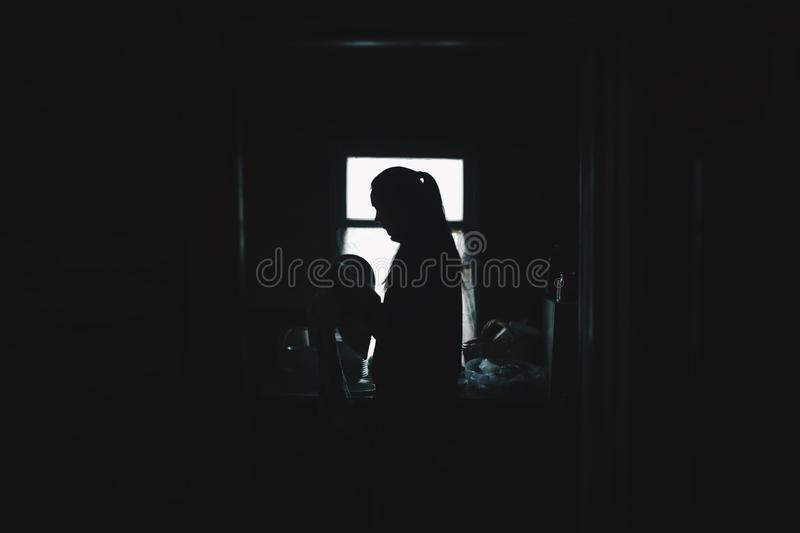 Silhouette of young girl washing dishes in the kitchen. stock photos