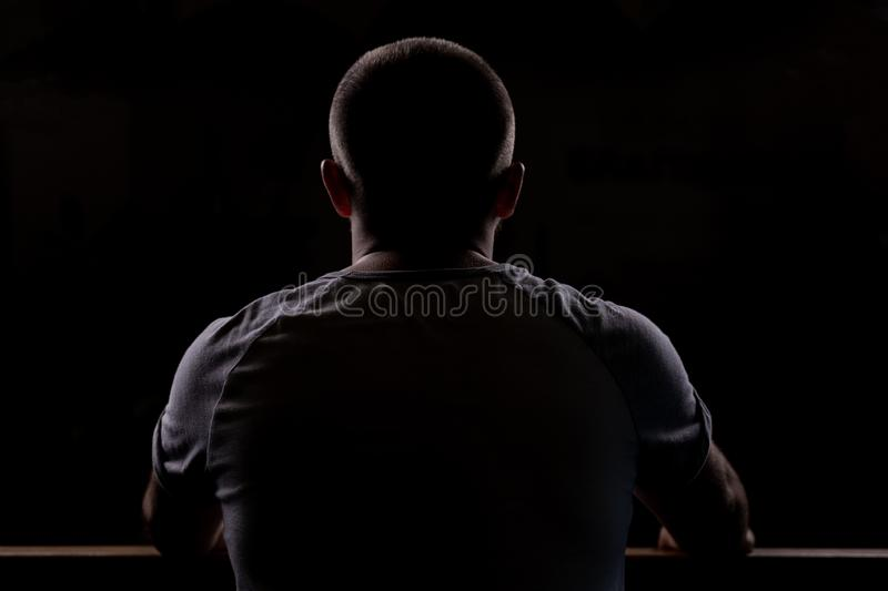Silhouette of a young guy who sits. Close-up view from behind. Backlight stock photos