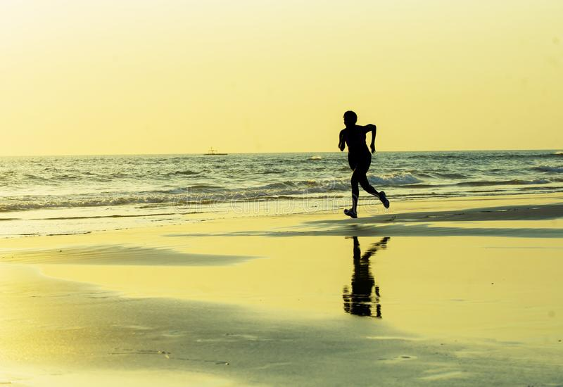 Silhouette of young happy and attractive African American runner woman exercising in running fitness sprint workout at beautiful b stock images