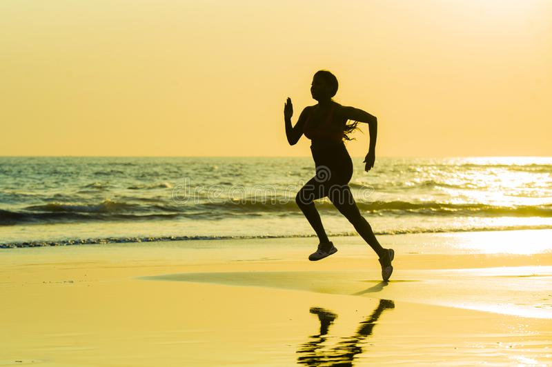 Silhouette of young happy and attractive African American runner woman exercising in running fitness sprint workout at beautiful b royalty free stock photography