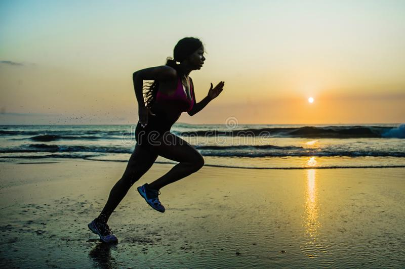 Silhouette of young happy and attractive African American runner woman exercising in running fitness sprint workout at beautiful b royalty free stock images