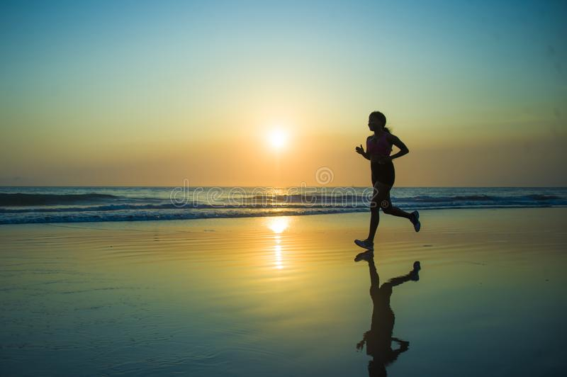 Silhouette of young happy and attractive African American runner woman exercising in running fitness workout at beautiful beach jo stock image
