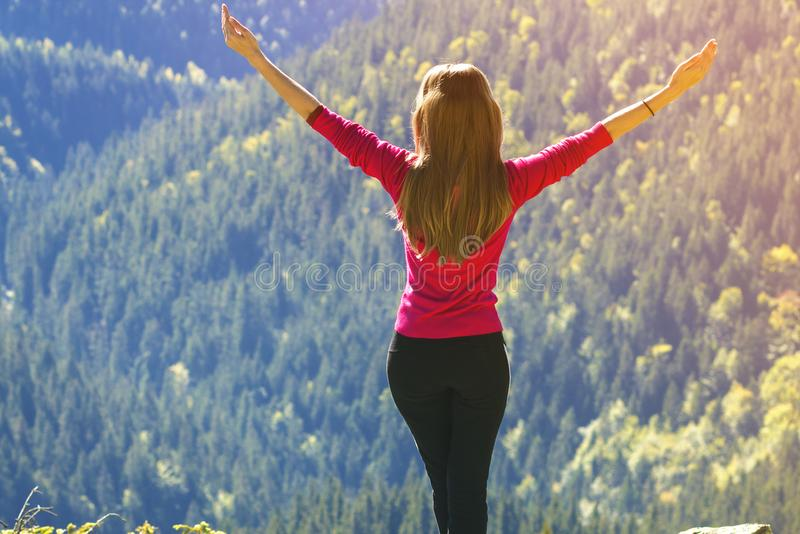 Silhouette of a young happy beautiful slim girl in red sweater s. Tanding on big rocks in mountains lifting hands. Tourism and traveling stock photography