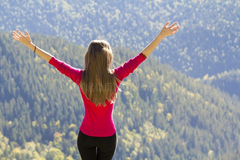 Silhouette of a young happy beautiful slim girl in red sweater standing on big rocks in mountains lifting hands. Tourism and trave stock photos