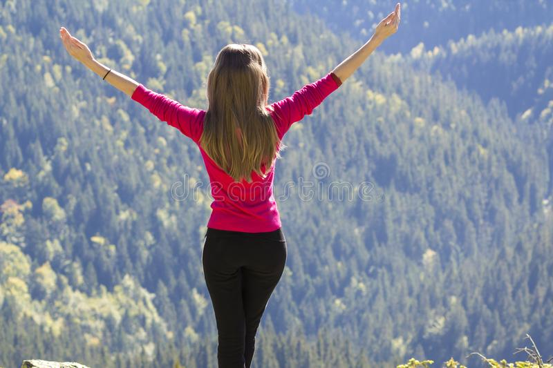 Silhouette of a young happy beautiful slim girl in red sweater standing on big rocks in mountains lifting hands. Tourism and trave stock image