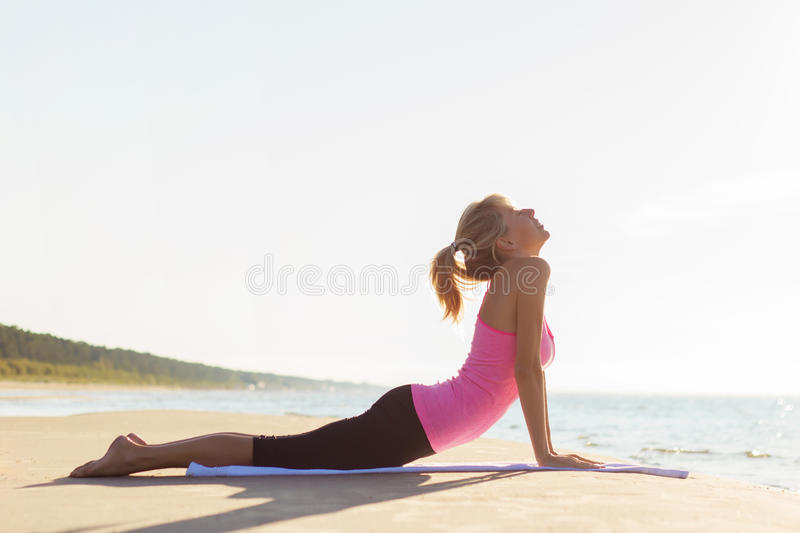 Silhouette of young healthy and fit woman practicing yoga stock images
