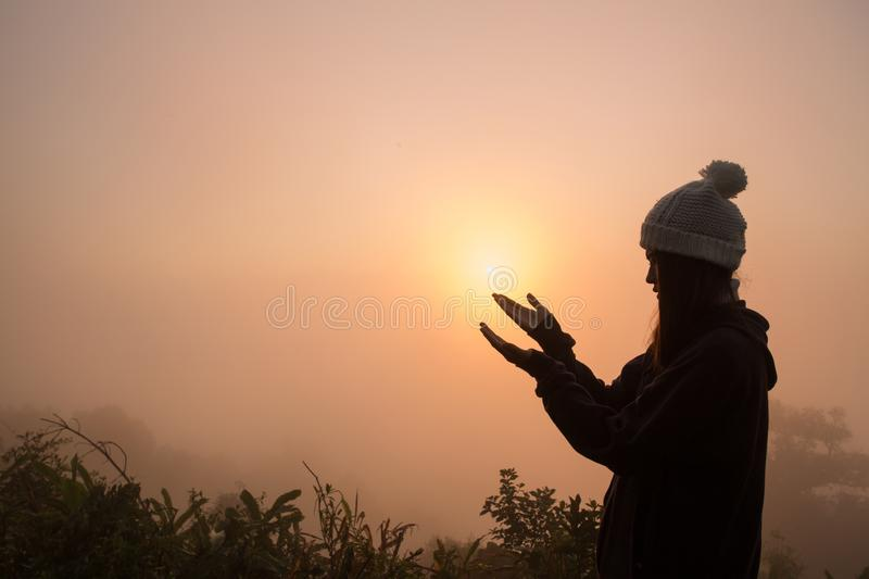 Silhouette of young human hands open palm up worship and praying to god at sunrise, Christian Religion concept background.  royalty free stock photos