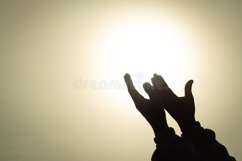 Silhouette of young human hands open palm up worship and praying to god at sunrise, Christian Religion concept background.  royalty free stock image