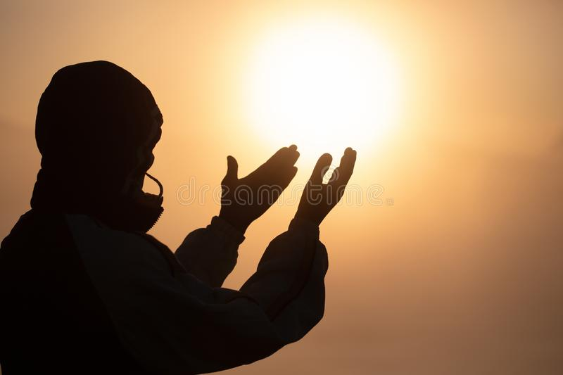 Silhouette of young human hands open palm up worship and praying to god at sunrise, Christian Religion concept background stock images