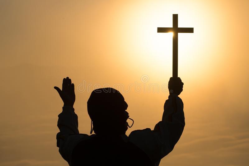 Silhouette of young human hands praying with a cross at sunrise, Christian Religion concept background royalty free stock images