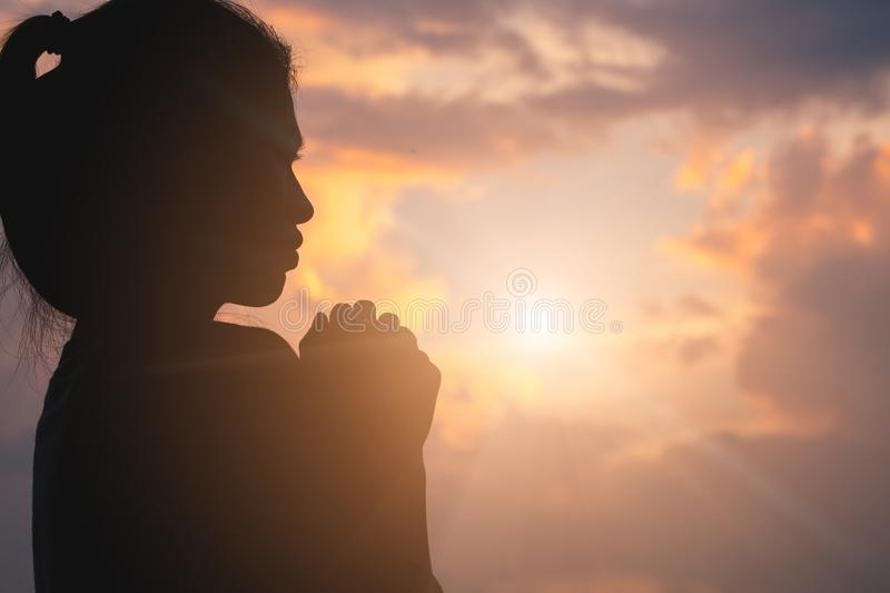 Silhouette of young human hands praying to god at sunrise, Christian Religion concept background royalty free stock images