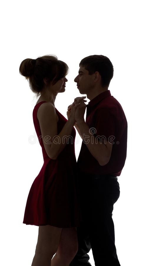 Silhouette of a young male and female in love on white isolated background, man touch hands of woman and dancing slowly, concept stock photos