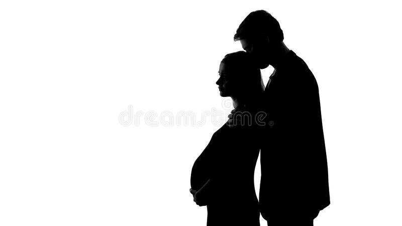 Silhouette of young male kissing sad pregnant woman, unhappy relationship stock photos