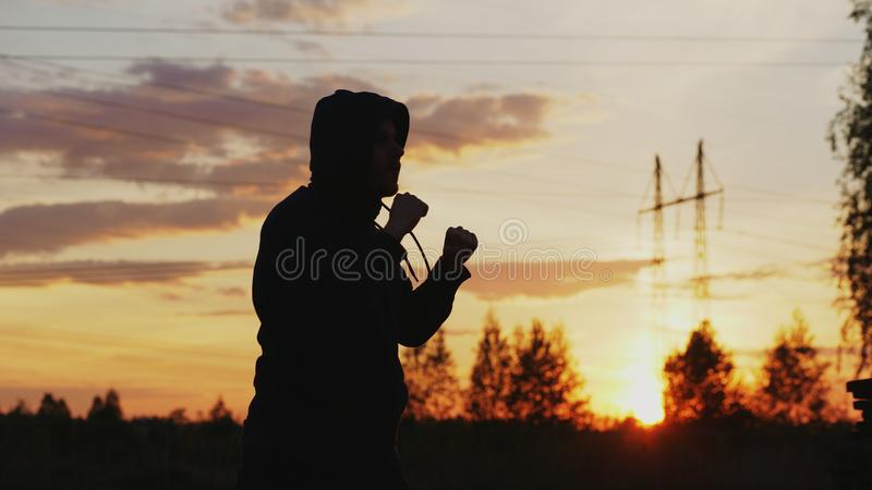 Silhouette of young man boxer training for kicking on sunset at city park royalty free stock photos