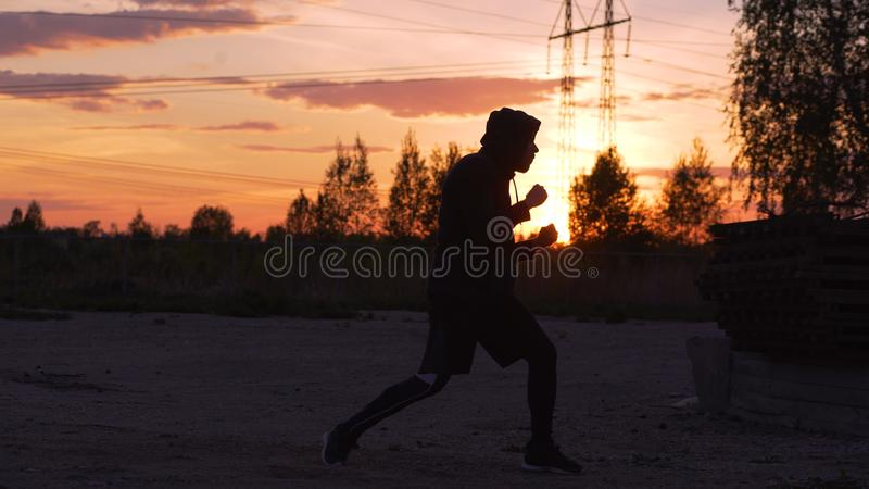 Silhouette of young man boxer training for kicking on sunset at city park royalty free stock photo