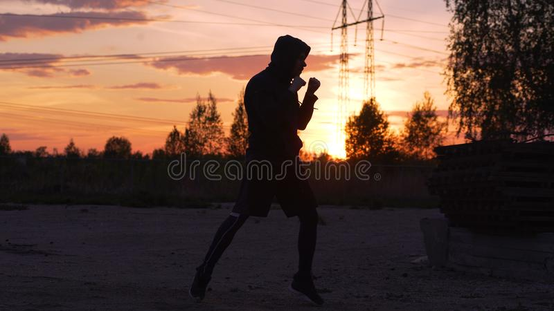 Silhouette of young man boxer training for kicking on sunset at city park royalty free stock photography