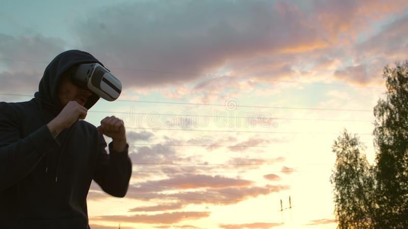 Silhouette of young man boxer in VR 360 headset training for kicking in virtual reality combat on sunset at city park stock photos