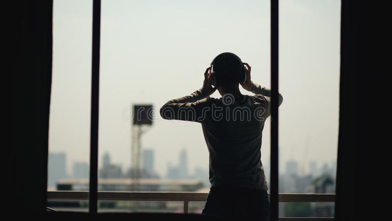 Silhouette of young man dancing ad listening music in wireles headphones stand on hotel room balcony stock images