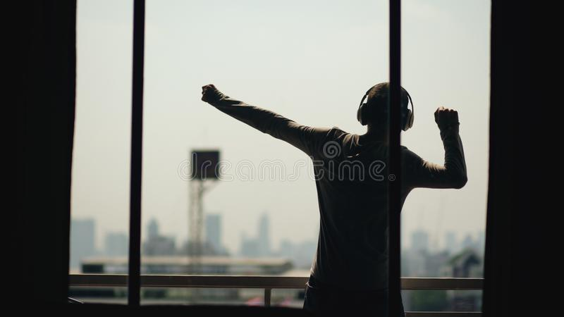 Silhouette of young man dancing ad listening music in wireles headphones stand on hotel room balcony royalty free stock photos