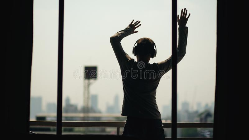 Silhouette of young man dancing ad listening music in wireles headphones stand on hotel room balcony stock photo