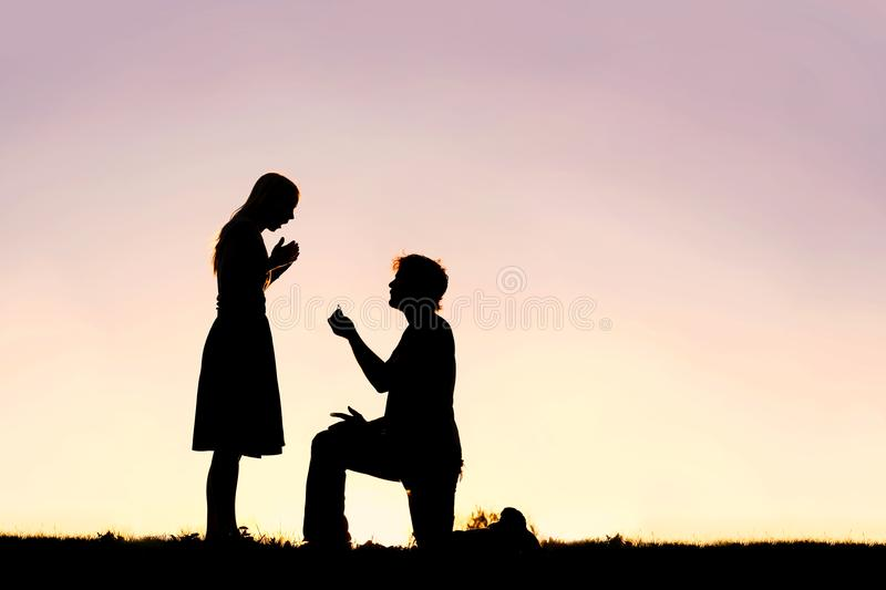 Silhouette of Young Man with Engagement Ring Proposing to Woman stock photos