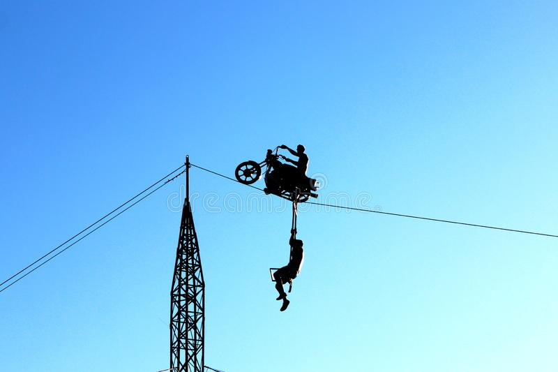 Action scene with motorcycle. Silhouette of a young man driving motocycle above on a wire carrying another young man - spectacular action performance stock photo