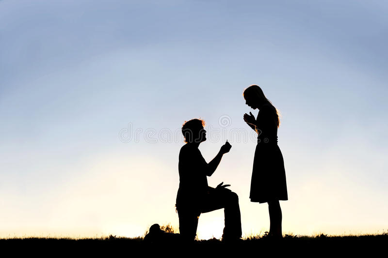 Silhouette of Young Man with Engagement Ring Proposing to Woman. A silhouette of a young man, down on one knee and holding a diamond engagement ring, proposing royalty free stock image