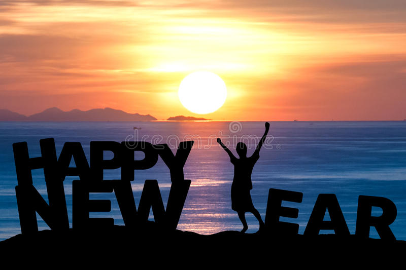 Silhouette young man extend arms make happy new year. Silhouette young man extend the arms more power on the sea and make the word happy new year while royalty free stock images