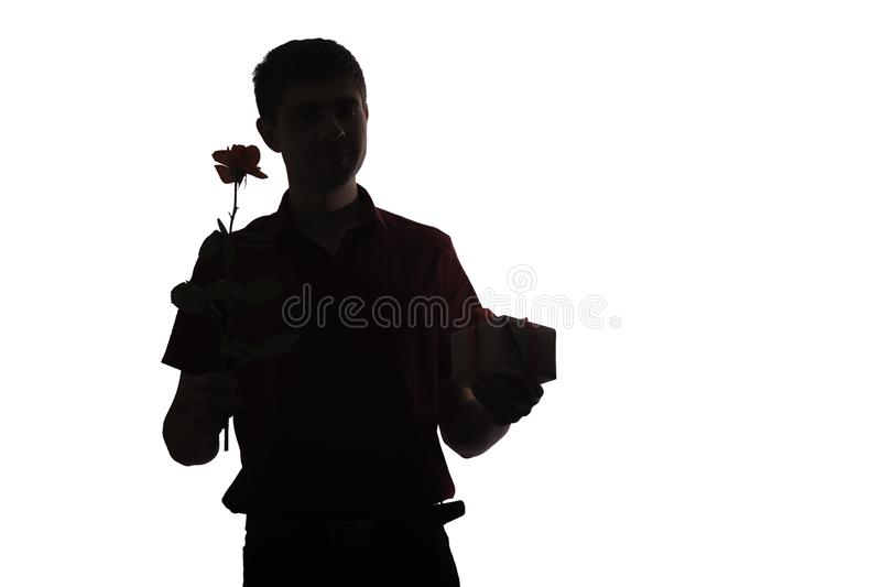 Silhouette of young man with a gift box and a rose flower for his beloved, boy congratulates on white isolated background, concept royalty free stock images