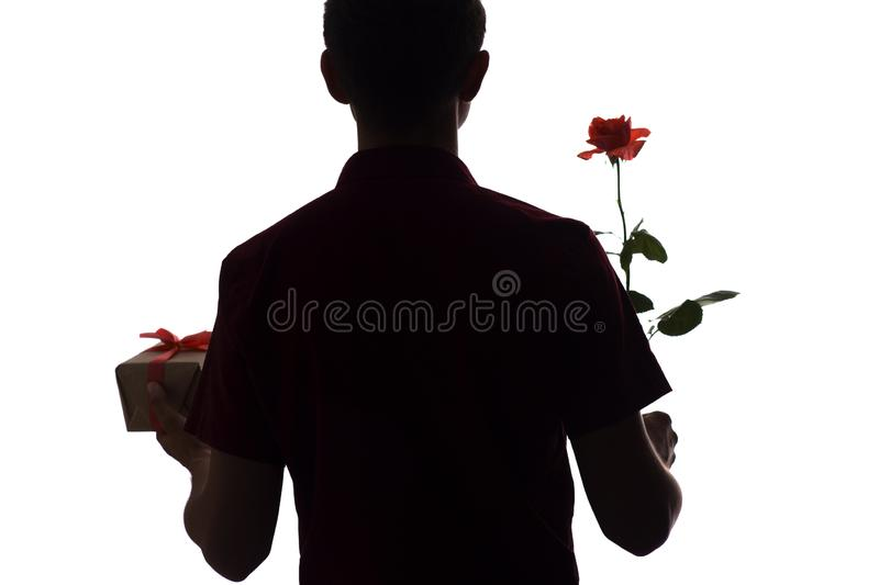 Silhouette of young man with a gift box and a rose flower for his beloved, boy congratulates on white isolated background, concept stock images