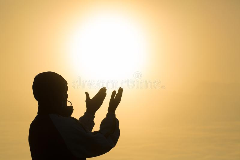 Silhouette of young man hands open palm up worship and praying to god at sunrise, Christian Religion concept background stock image
