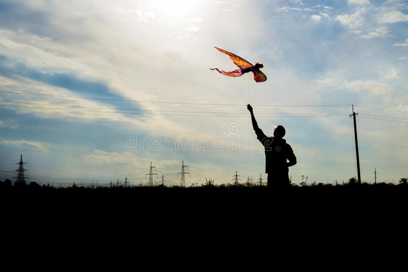 Silhouette of a young man holding a kite flying in beautiful blue sky with clouds.  royalty free stock photography