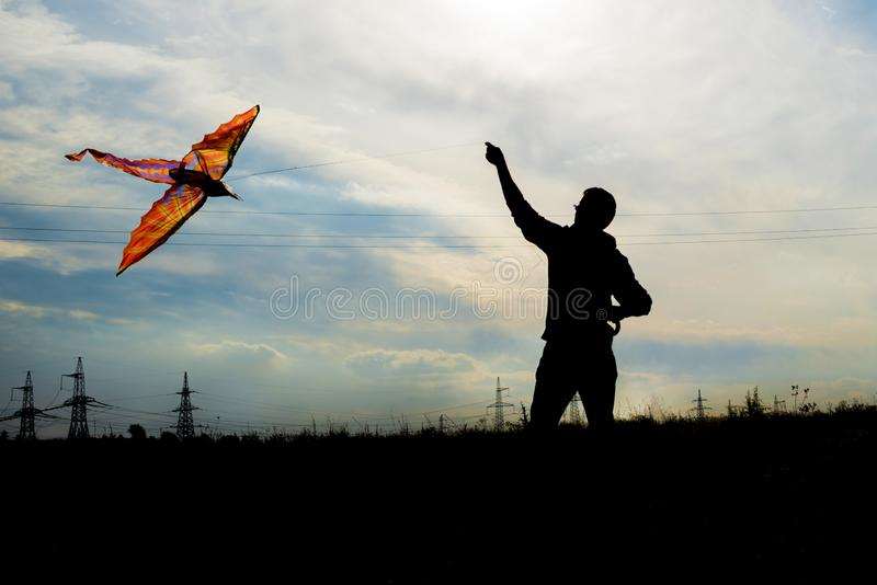 Silhouette of a young man holding a kite flying in beautiful blue sky with clouds.  stock photo