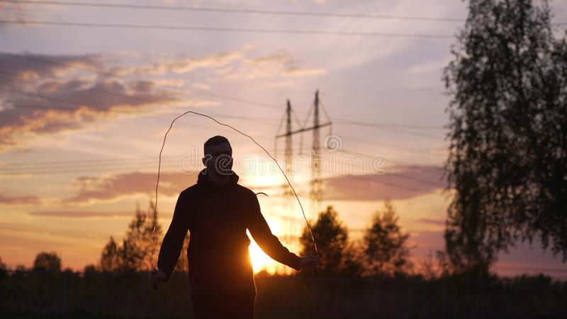 Silhouette of young man kick boxer training with skipping rope on sunset at city park royalty free stock photography