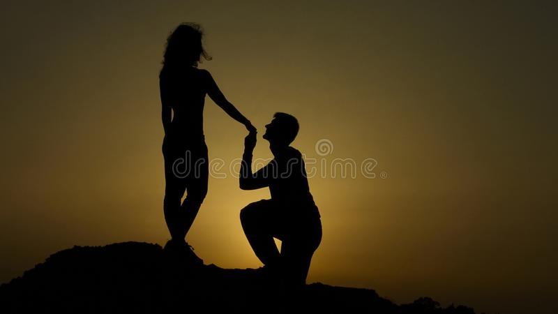Silhouette of young man proposing to girlfriend on his knee, romantic engagement. Stock footage stock image