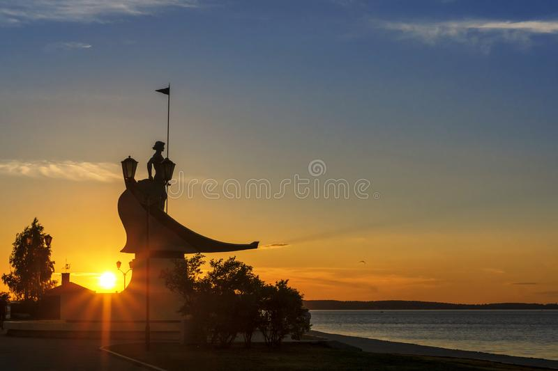 Silhouette of sculpture of man on boat on sunset background on lakeside. Silhouette of a young man`s sculpture on a boat on a sunset background on the lake stock photos