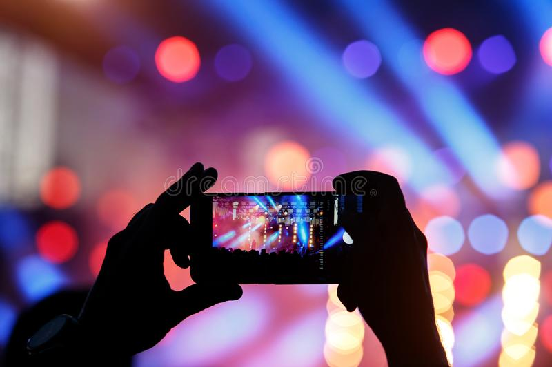 Silhouette of young man, taking photo rock concert on the mobile phone stock photo